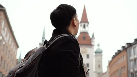 münchen : Young Asian man tourist traveling in city centre in Europe. Male backpacker walking in Marienplatz square, Munich, Germany. Traveling to Europe concept Stock mozgókép