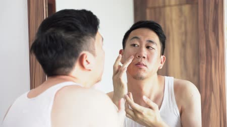salle d eau : Confused Asian young man in white shirt squeezing pimples in front of mirror at home Vidéos Libres De Droits