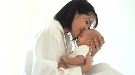 собственность : Side view of caring young Asian mum in white wear holding own infant kissing newborn son at home