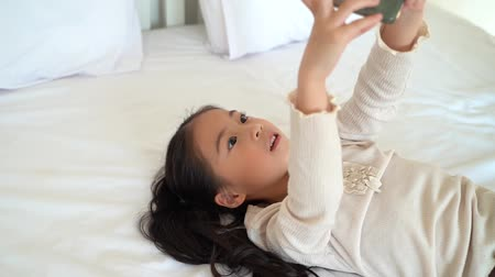 Side view of adorable Asian girl in casual wear playing video game on smartphone lying on bed in house 動画素材