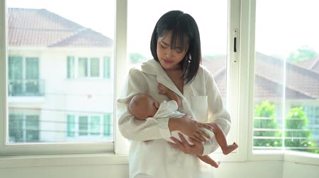 patting : Caring Asian mother holding newborn son on hands little baby sleeping in bedroom of modern house Stock Footage