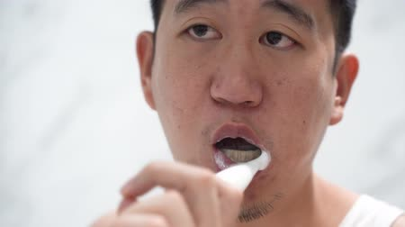 creme dental : Back view of Asian guy in white shirt brushing teeth with an electric toothbrush in front of mirror in bathroom Stock Footage
