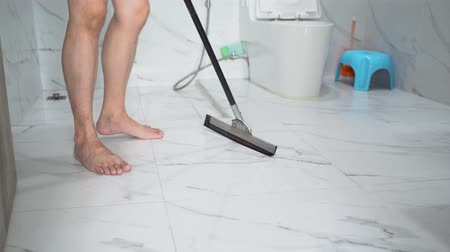 tiled floor : Man in home clothing standing and using swab for washing tiled floor in modern bathroom Stock Footage