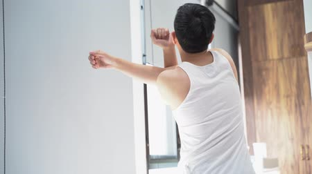 dozen : Back view of black haired male in home clothing standing and stretching arms in bedroom on sunny morning Stock Footage