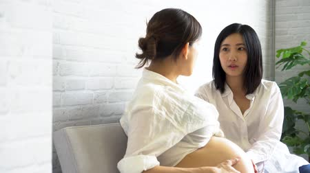 Young Asian pregnant woman talking with another female expectant at antenatal class in the hospital 動画素材
