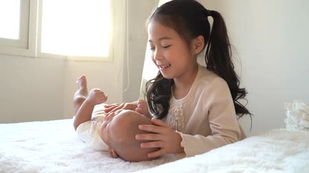 kinderbett : Asian family of cute little sister touching newborn baby boy brother. Toddler kid and new sibling relax in a white bedroom at home with love and tenderness