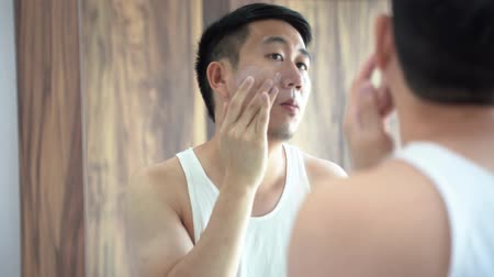 sunblock : Back view of Asian male in white shirt using a skincare cream for face in front of mirror in bathroom
