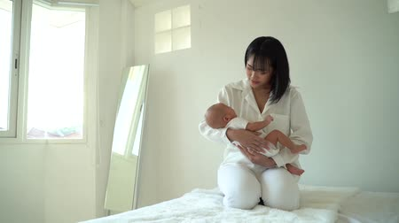 puericultura : Caring Asian mother holding newborn son on hands little baby sleeping in bedroom of modern house Stock Footage