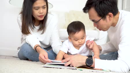 education kids : Happy modern Asian parents sitting on floor with cute infant boy and reading fairy tale while enjoying time together at home