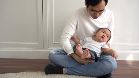 livingroom : Asian hungry boy crying for attention whlie parents trying to comfort him. Parenthood in Asia concept Stock Footage