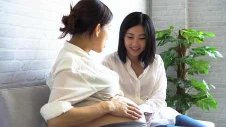 Young Asian pregnant woman talking with another female expectant at antenatal class in the hospital Stock Footage