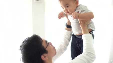 pai : Young adult 30s Asian father lifting his little own son up flying in the air in bedroom at home. Family time and fatherhood concept in Asia