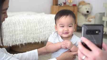Cute excited little Asian boy enjoying funny video on mobile phone and laughing while standing in room supported by happy mom