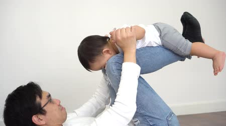 Joyful Asian boy playing airplane with parenting dad in the living room at home. Father is carrying innocent son up on his legs ready to fly. Fatherhood in Asia concept Stock Footage
