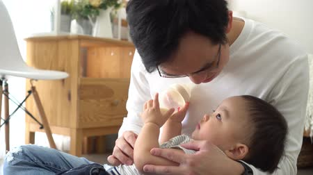 puericultura : Asian family of young father feeding a baby boy from milk bottle at home