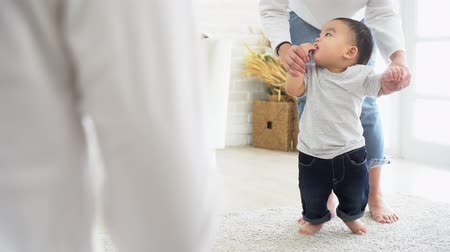 Asian baby boy toddler taking first steps. Family of father and mother encouraging their son learning to walk at home Stock Footage