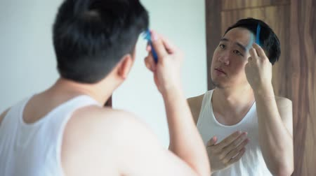 Back view of young Asian man in white shirt combing hair in front of mirror in bathroom Wideo