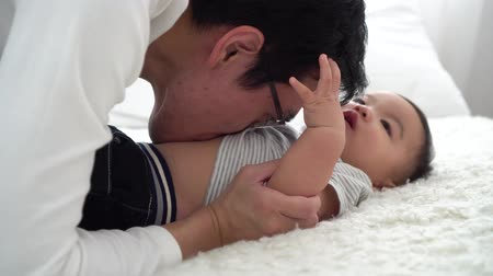 Family of young Asian father tenderly kissing his baby boy on his stomach with his wife. Man and woman enjoying their time with child