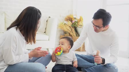 Asian family of father and mother playing toy doll with their son on sitting on the floor at home. Young man and woman enjoying family time together Stock Footage