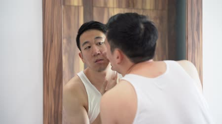 Confused Asian young man in white shirt squeezing pimples in front of mirror at home 動画素材