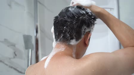 Back view from below of black haired naked man washing hair with shampoo while talking shower in bathroom Wideo