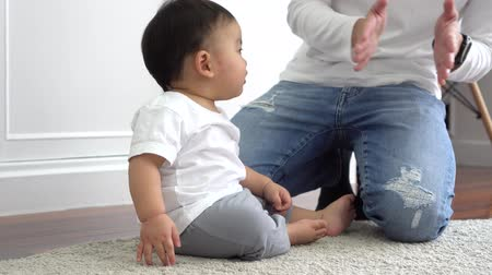 Happy Asian family of young father playing games and clapping hands with baby boy child at home, parent enjoying family time Wideo