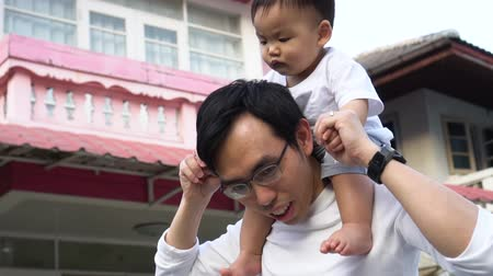 Asian father giving a piggyback ride for little son in front of the house. Dad and child enjoying warm family time Filmati Stock