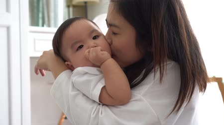 Asian young adult mother kissing joyful son in living room. Love of mother concept.