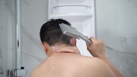 Back view of black haired undressed man pouring hot water from shower head in modern bathroom