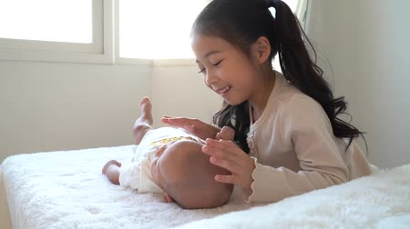 Asian family of cute little sister touching newborn baby boy brother. Toddler kid and new sibling relax in a white bedroom at home with love and tenderness