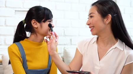 sharing : Smiling adult Asian woman using makeup brush and applying blusher on cheeks of young charming daughter while sitting together on sofa in living room