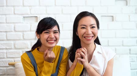 torcendo : Asian family of mother and daughter smiling while cheering at home and watching TV on white brick wall background