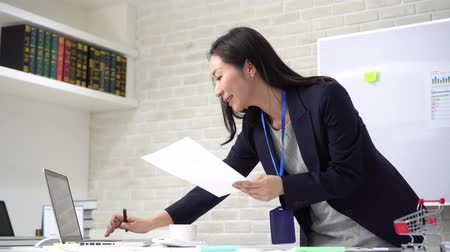 administracja : Satisfied Asian woman in formal outfit with badge smiling and reading paper while standing by table with marketing plan and laptop in office