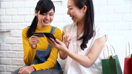 Happy smiling Asian mother and daughter in casual outfit browsing smartphone and using credit card while man family sitting on sofa with shopping bags