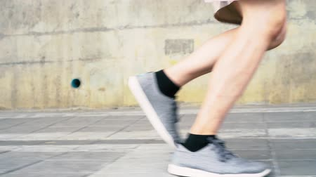 Low section of man in sports shoes jogging outdoors on city footpath 動画素材