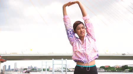 Young Asian sportswoman stretching outdoors in morning. Female fit woman doing a morning stretch on riverside bridge