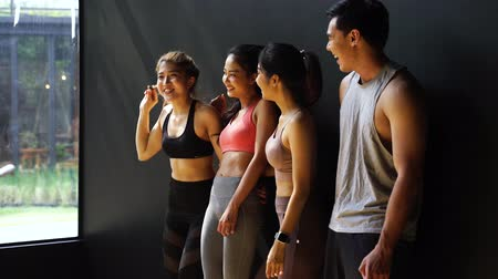 Happy smiling man and women having fun talking in gym. Group of young people relaxing in gym after workout training with black background. 動画素材