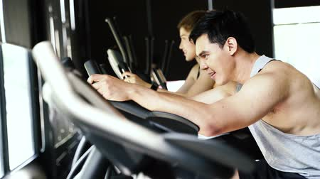 ciclismo : Side view of attractive Asian woman and man riding on the spinning bike at the gym. Young couple exercising and doing cardio workout together
