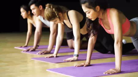 trabalhar fora : Group of Asian women and man doing push-up exercises on yoga mats in aerobics class. Young sporty people working out together on the floor in gym studio. Fitness Class Concept