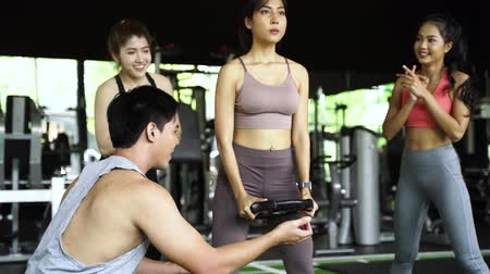 Group of people cheering on their Asian female friend doing squats with a weight plate in fitness gym. Working out together as a teamwork. Encouragement and togetherness concept