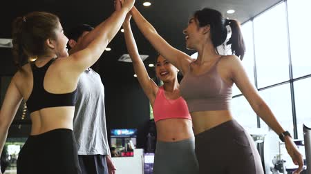 пять : Smile man and women making hands together in fitness gym. Group of young people doing high five gesture in gym after workout. Happy successful workout class after training. Teamwork concept