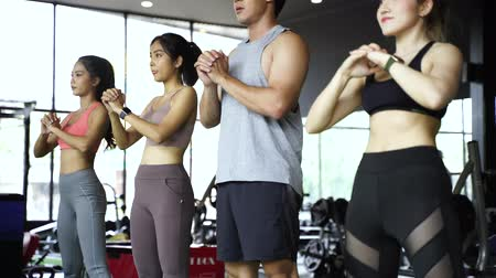 squatting : Group of athletic young Asian people in sportswear doing squat and exercising at the gym. Intense workout and healthy lifestyle concept