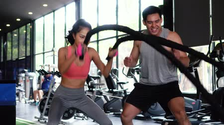 Asian personal trainer coaching a bodybuilding woman to perform crossfit battle ropes exercise in the fitness gym. Workout training coach business concept