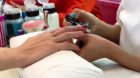 Close-up of woman hands at beauty salon receiving a manicure and nail care process by manicurist. Young female getting nails done by beautician.