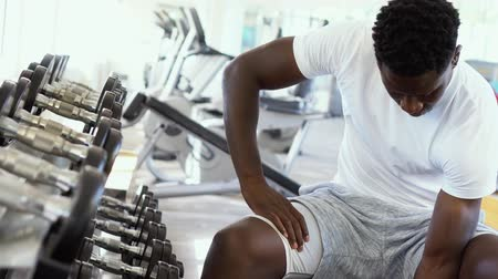 biceps curls : Young African American man sitting and lifting a dumbbell close to the rack at gym. Male weight training person doing a biceps curl in fitness center. Stock Footage