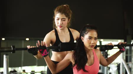Asian personal trainer coaching a bodybuilding woman to perform the exercise squat with barbell in the fitness gym. Weightlifting and workout training concept