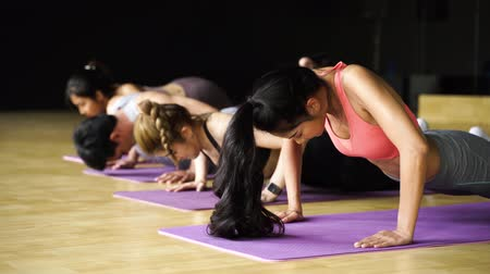 Group of Asian women and man doing push-up exercises on yoga mats in aerobics class. Young sporty people working out together on the floor in gym studio. Fitness Class Concept