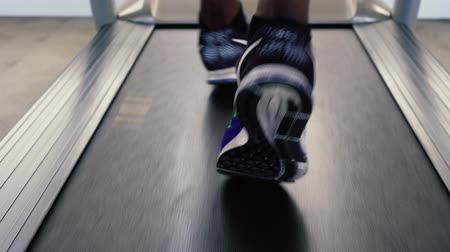 tornacipő : African American sportsman in blue sneakers working out on electric treadmill in fitness club. Faceless male runner running on treadmill. Stock mozgókép