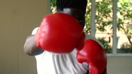 Athletic African American sportsman in red boxing gloves attacking during workout. Male boxer punching in gym.