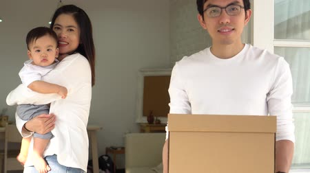 Cheerful Asian parents holding cute baby and box with belongings looking at camera while moving into new house. Young couple family relocation.